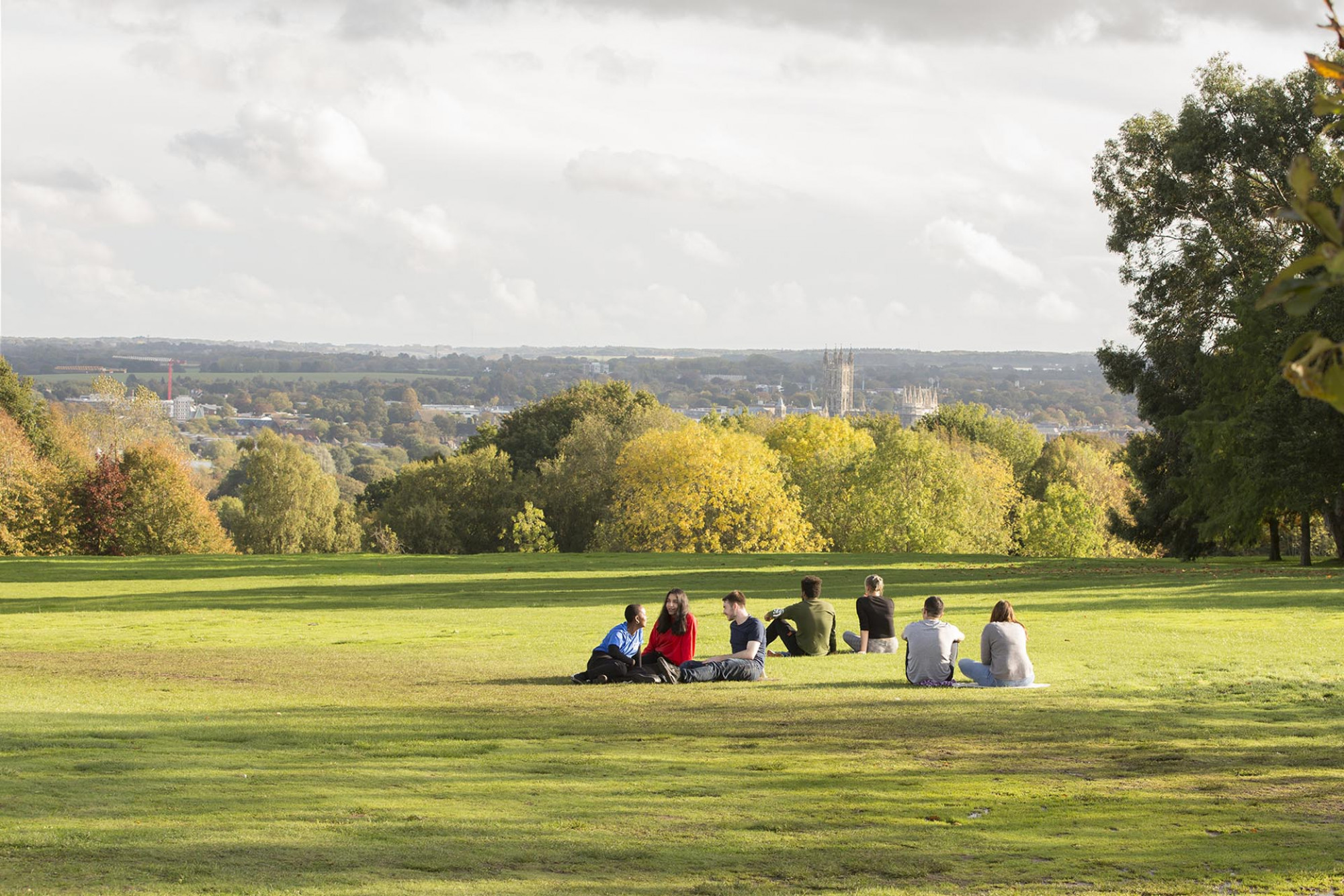 Students sit on the grass overlooking Canterbury