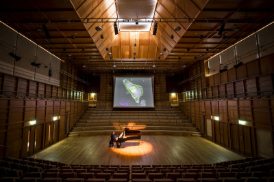 Pianist in Colyer-Fergusson Concert hall plays in front of screen showing cells