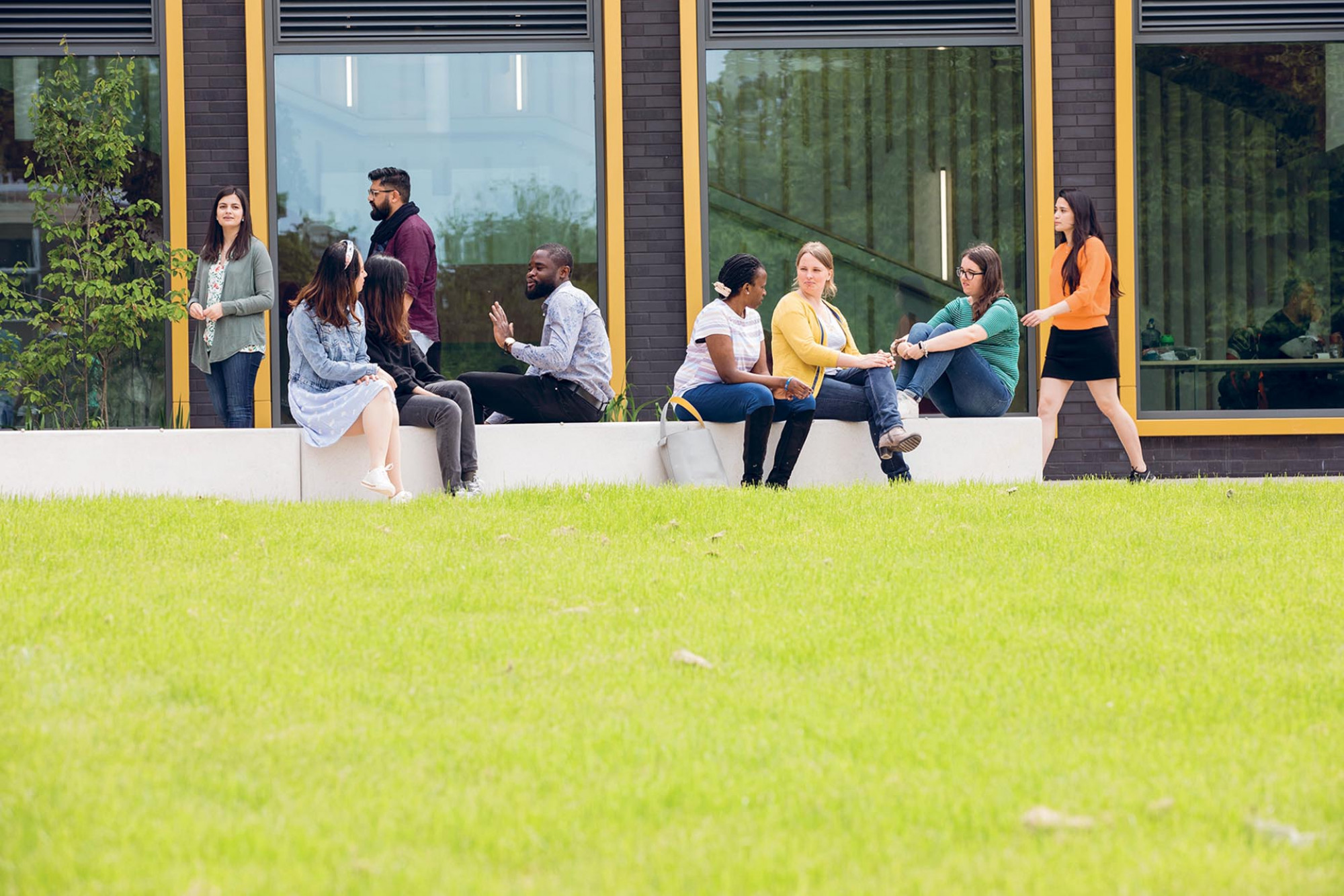 A group of postgraduates sit outside the Kennedy Building on the Canterbury campus