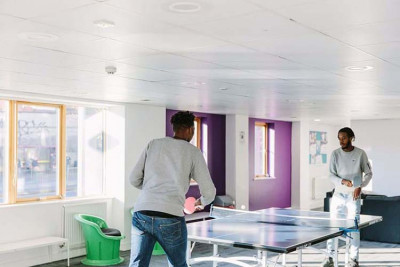 Male student playing table tennis in Pier Quays social space