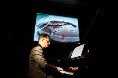 Pianist playing in front of projector screen