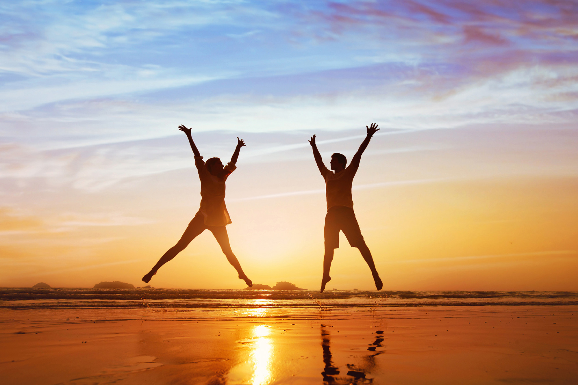 Silhouette of man and woman jumping with arms in the air on a beach during sunset