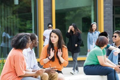 Students sat outside talking at the Canterbury campus.
