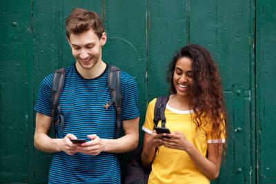 Two young students smiling and looking at their phones