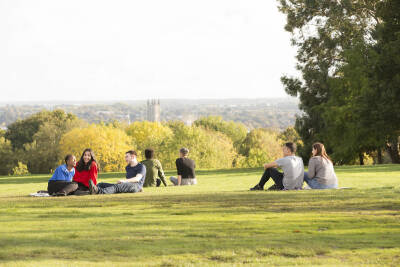 Students sitting on the green enjoying the view over the city and Canterbury Cathedral.