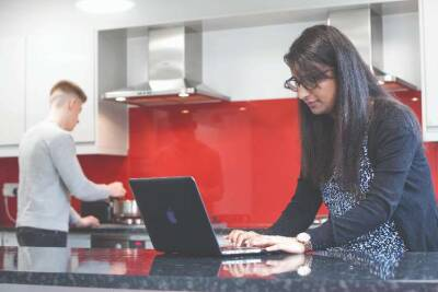 Two students, one on laptop, one cooking in student accommodation