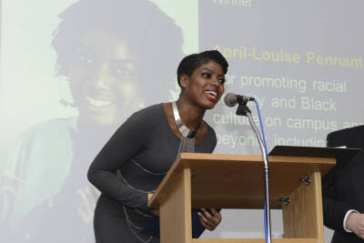 A student accepting an award in front of a screen which says 'Promoting racial equality and Black culture on campus'.
