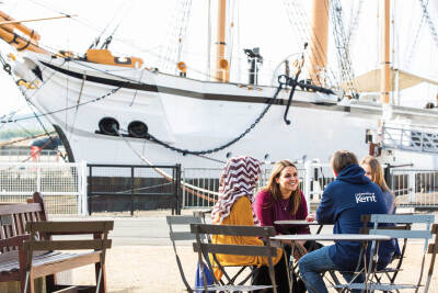 4 students sitting at a table in front of a ship in Medway dockyard