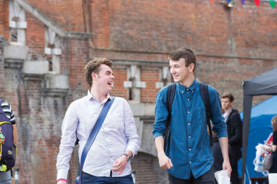 Two male students walking and laughing