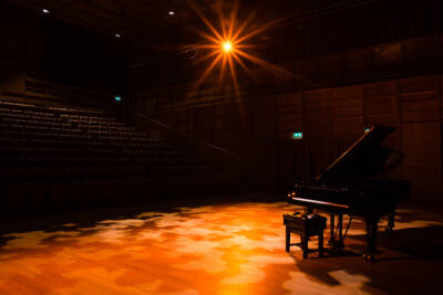 Hall in darkness with a spotlight on a grand piano