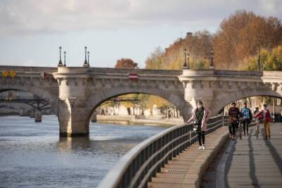 Young adults walking beside the river in Paris