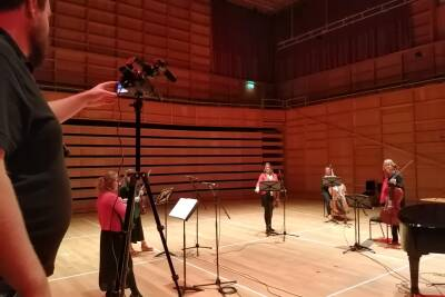 Cameraman filming the string players in rehearsal in the concert-hall