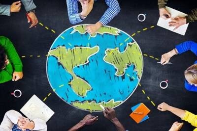 People sitting around at illustration of a globe
