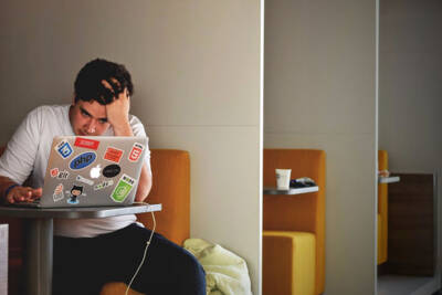 Guy by laptop looking stressed