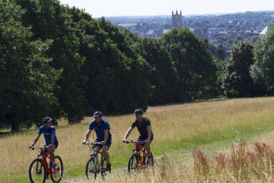 Three cyclists on field route through campus with the Cathedral showing in background