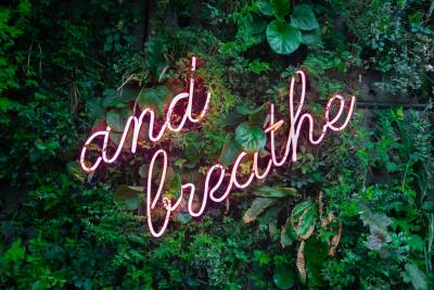 """""""And breathe"""" neon light with greenery background"""