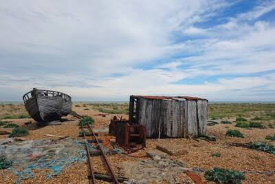 Wrecked boat and shed on pebbled beach of Dungeness