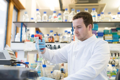 Male student using pipette in research lab