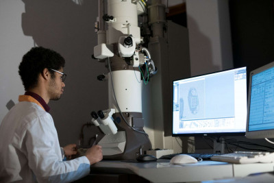 Male student using an electron microscope