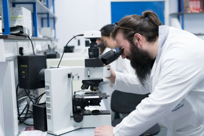 Male and female student using microscopes