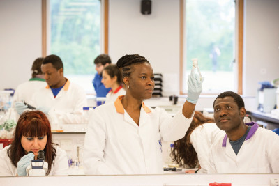 Female student examining a glass flask