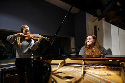 Girl playing piano smiles towards girl playing the violin