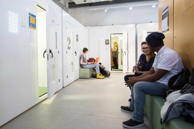 Students sit ourside practice spaces. Two are chatting, another uses a laptop. A practice room door is ajar.