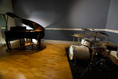 Studio with a wooden floor and grey walls, containing a grand piano and a drum kit