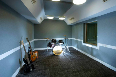 A room containing a drum kit and two guitars. The room has one internal window and bright ceiling lights.