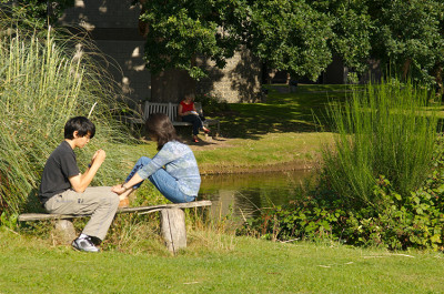 Students relax by Keynes College duck pond