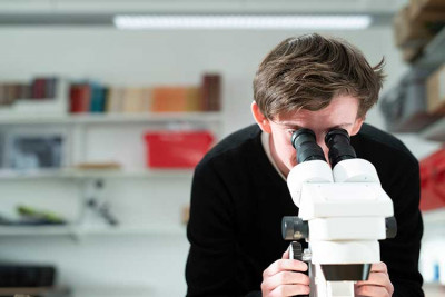 Male student looking into microscope