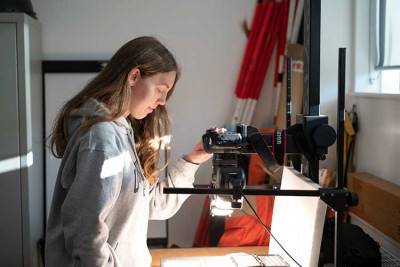 Girl in grey hoodie using camera to photograph artefacts
