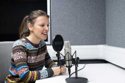 Woman in multi-coloured jumper speaking into a circular microphone in a studio