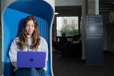 Student with long brown hair, grey sweatshirt, sitting in a blue chair and using a purple laptop