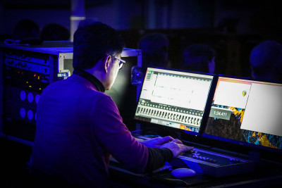 Student looking at two screens in the Music and Audio Arts Sound Theatre.