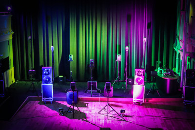 The Music and Audio Arts Sound Theatre set up in front of a closed curtain. Pink and green lights shine on it.