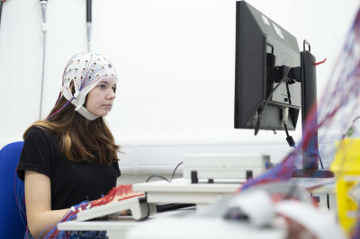 Student with EEG cap in front of computer screen