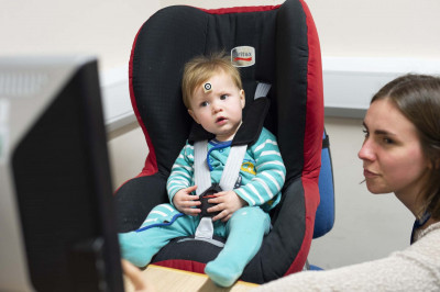 Young child in seat and in front of screen with psychologist alongside
