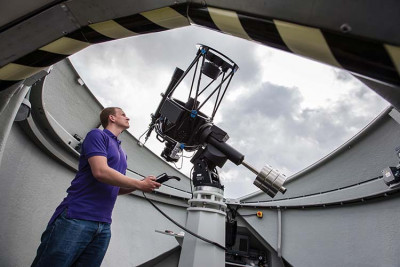 Male student operating a telescope in the Beacon Observatory.