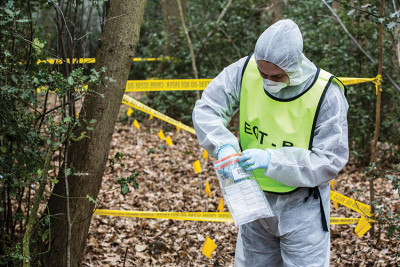 Student in protective clothing placing material in an evidence bag at an outdoor mock crime scene.