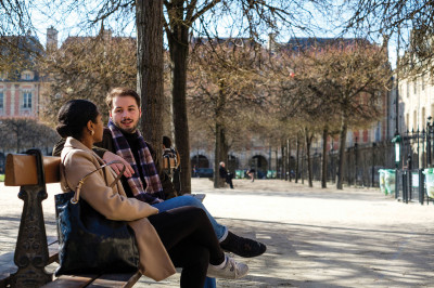 Two students talking on a bench in a park in Paris