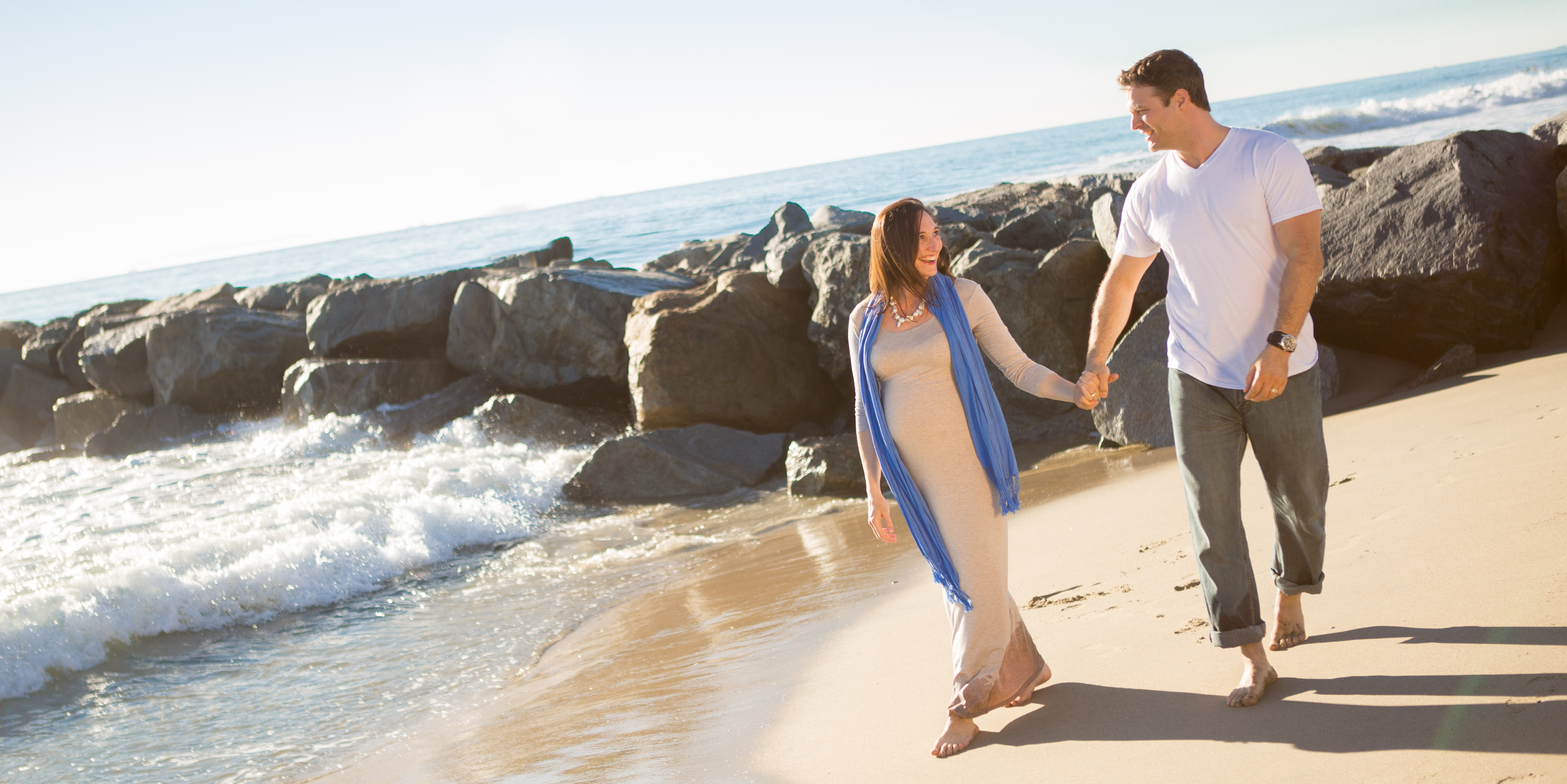 Staged photo of pregnant woman and handsome husband strolling on beach
