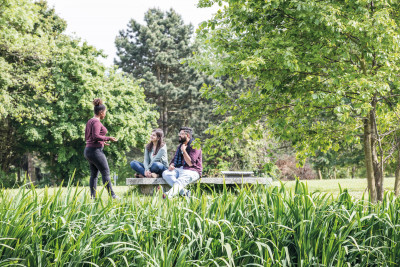 A group of 3 students sat outside on a bench talking surrounded by trees.
