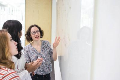 Three women talking in front of a whiteboard