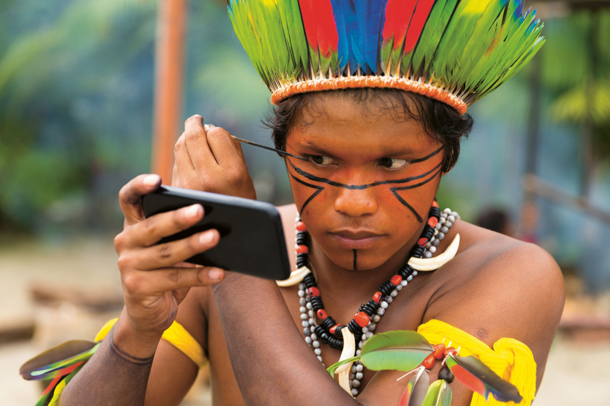 Native Brazilian man in feathered headdress applies black face paint in traditional patterns using mobile phone as mirror