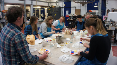 Students painting their masks in the School of Arts dedicated workshop.