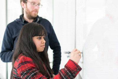 Girl with long dark hair and red check jacket writing on whiteboard