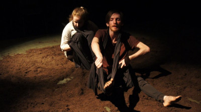 Two performers sit in moody lighting surrounded by black drapes and mud.