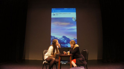 Two students in The Aphra theatre, with back projection.