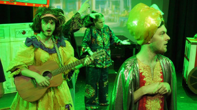 The panto dame plays a guitar, while the villain looks offstage.